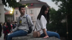 Young couple sitting on a rock and admires old European city - romantic evening Stock Footage