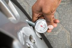 Close-up Of Person Hand Holding Pressure Gauge For Measuring Car Tyre Pressur - stock photo