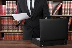 Close-up Of Male Lawyer Removing Papers From Briefcase In Office Stock Photos