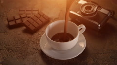 White cup with chocolate bar and retro camera on texture table Stock Footage
