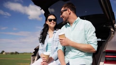 Happy couple with coffee at hatchback car trunk 26 Stock Footage