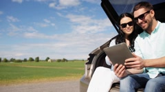 Happy couple with tablet pc at hatchback car trunk 33 Stock Footage