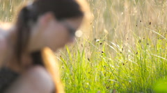 Woman working with focused tall grass in background 4K Stock Footage