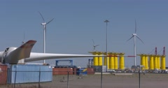 Parts of wind turbines stored on quayside in Eemshaven, The Netherlands Stock Footage