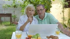 Couple talking through a laptop in the garden. Stock Footage
