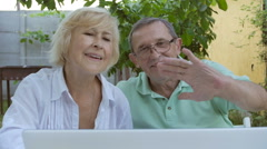Elderly couple waving his hands in laptop webcam. - stock footage
