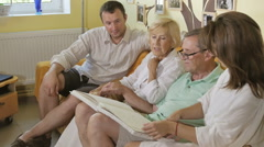 Family sits on a sofa and consider the book. Stock Footage