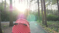 Ufa, Russia. - August 3: Mother with baby in stroller walking in park, August 3 Stock Footage
