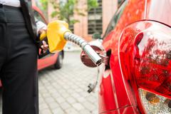 Close-up Of Businesswoman's Hand Refueling Car's Tank By Holding Petrol Pump  - stock photo