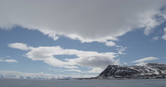 Time lapse - Clouds race over mountain spit over sea ice on sunny day Stock Footage