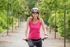 Young Female Cyclist Riding Her Bicycle With Safety Helmet - stock photo