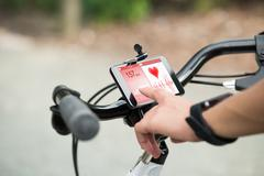 Close-up Of Human Hand Pointing At Smart Phone Showing Heartbeat Rate On Bicy Stock Photos