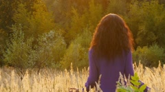 Young girl walks on field with tall long grass on sunset, slow motion. Stock Footage