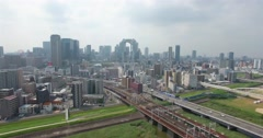 Descending aerial view of Osaka city train transport into CBD Stock Footage
