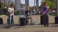 Young street musicians playing rock'n'roll outdorrs on street, slow motion. Stock Footage