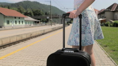 Female person walking with suitcase on train station 4K Stock Footage