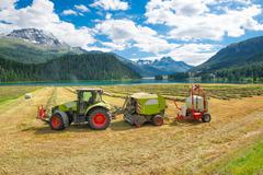 Tractor working the hay bales and creates fully automatic Stock Photos
