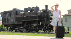 Woman with travel suitcase and locomotive in background 4K Stock Footage