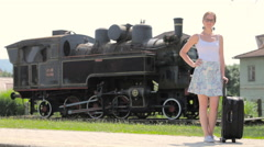 Woman dressed in skirt posing with travel suitcase and locomotive 4K Stock Footage