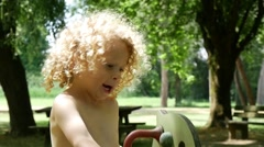 Happy little blond boy swinging in the park on a sunny day - stock footage