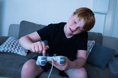 Unhappy Boy Sitting On Sofa Pressing Button Of Joystick - stock photo