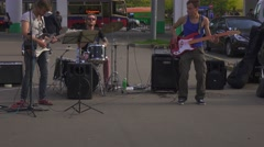 Young street musicians playing rock'n'roll outdorrs on street. Stock Footage