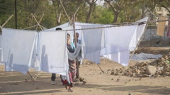 Woman hanging washed sheets on line,Indore,India Stock Footage