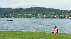 A woman sitting  look the lake the August 2, 2016 Worthersee, Austria Stock Footage