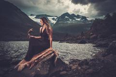 Nordic goddess in ritual garment with hawk near wild mountain lake in Innerdalen - stock photo