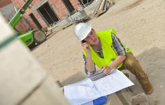Foreman using walkie-talkie on construction site Stock Photos