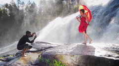Couple Doing Fashion Shoot By Waterfall With Smart Phone - stock footage