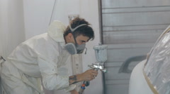 Mid shot Worker paints a car in white colour Stock Footage