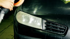 Close up shot worker polish car headlight with special tools - stock footage