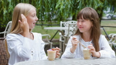 Two smiling girls or Happy children with ice cream outdoors Stock Footage
