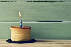 lit birthday candle on a cheesecake - stock photo