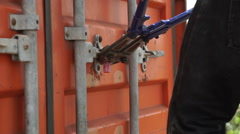 Pincer breaks the lock of a container, black hands N. Stock Footage