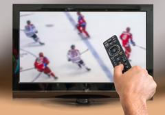 Man is watching hockey match on TV and holds remote controller in hand Stock Photos