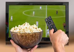 Man is watching football match on TV and holds remote controller and popcorn  Stock Photos