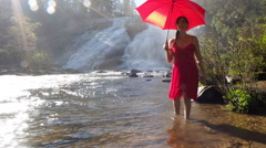 Beautiful Woman In Red Dress Holding Red Umbrella By Waterfall - stock footage