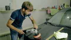 Mid shot Worker polish black car with special tools Stock Footage