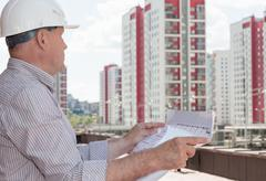 An engineer examining blueprints - stock photo
