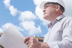 A construction worker man in white helmet holding blueprints on a background - stock photo