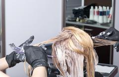 A blonde female client coloring hair in hairdressing salon - stock photo