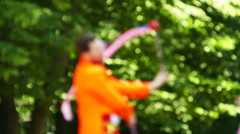 Slow motion. Smiling juggler with tapes in city park. Blurred scene - stock footage