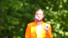 Slow motion. Smiling juggler in city park. Blurred scene Stock Footage