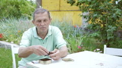 A man lights a pipe with tobacco. Stock Footage