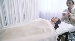 Beautician doing ultrasonic face treatment at beauty spa Stock Footage
