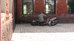 Male sportsman repairing his enduro motorcycle Stock Footage