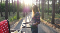 Ufa, Russia. - August 3: Mother with baby in stroller walking in park, August 3 - stock footage