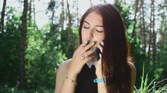 Young woman smoking a cigarette outdoor in slow motion - stock footage